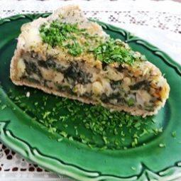 Fatia de torta de espinafre, queijo meia cura e passas.